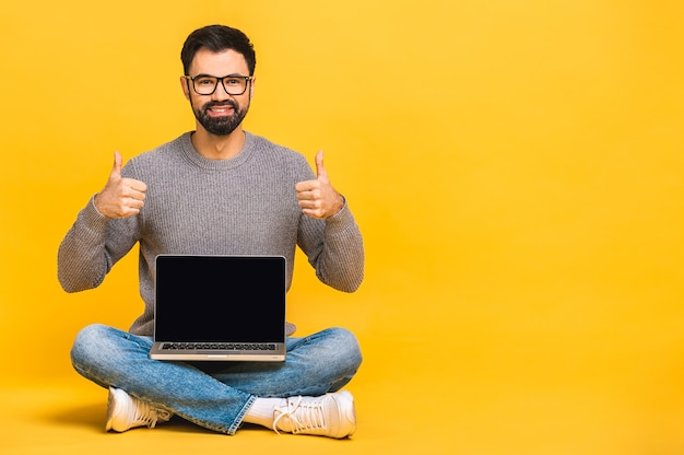 Portrait of a happy young bearded man in casual holding laptop computer while sitting on a floor isolated over yellow background