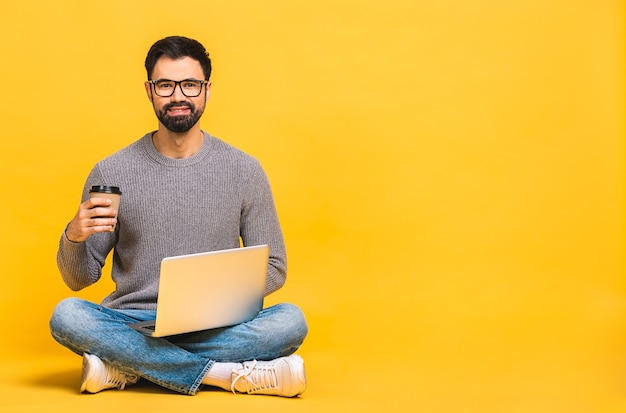 Portrait of a happy young bearded man in casual holding laptop computer while sitting on a floor isolated over yellow background.