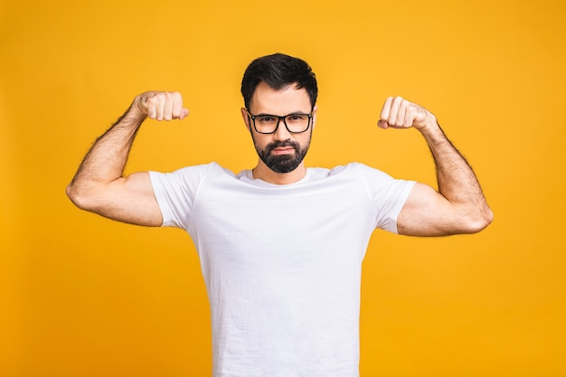 Portrait of a happy young bearded man dressed in t-shirt showing biceps isolated over yellow background. Premium Photo