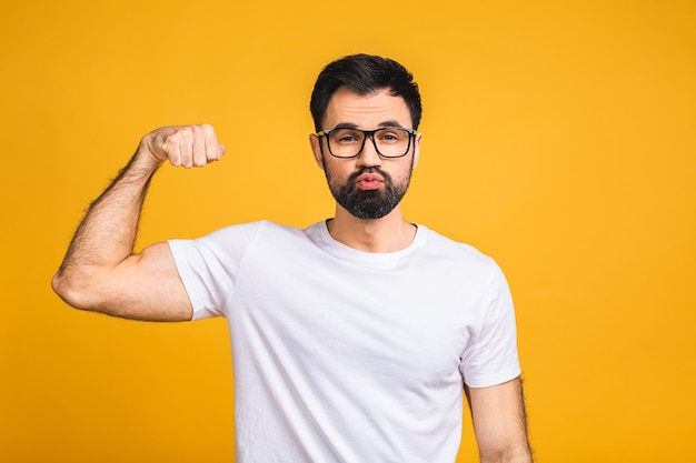 Portrait of a happy young bearded man dressed in t-shirt showing biceps isolated over yellow background.