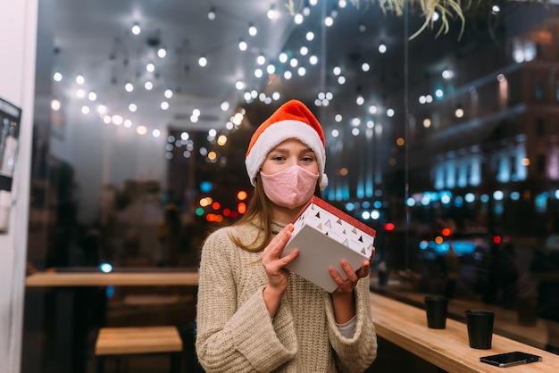 肖像画幸せな若い美しい女性は、ギフトボックスを保持し、カフェで笑顔