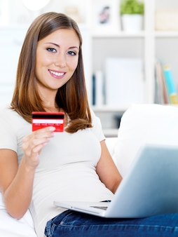 Portrait of happy young beautiful woman holding credit card and using laptop