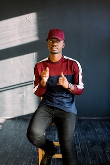 Portrait of happy young black african guy in red baseball cap sitting in a studio on a wooden chair on a dark background .