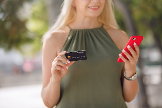 Portrait of a happy young blonde girl while holding mobile phone and plastic credit card