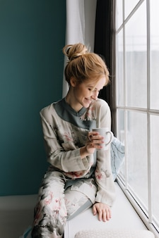 Portrait of happy young blonde spending morning looking through big window with cup of coffee or tea, staying at home. turquoise wall. wearing silk pajamas in flowers, hair up.
