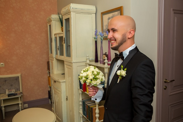 Portrait of happy young bridegroom with bouquet in hands smiling