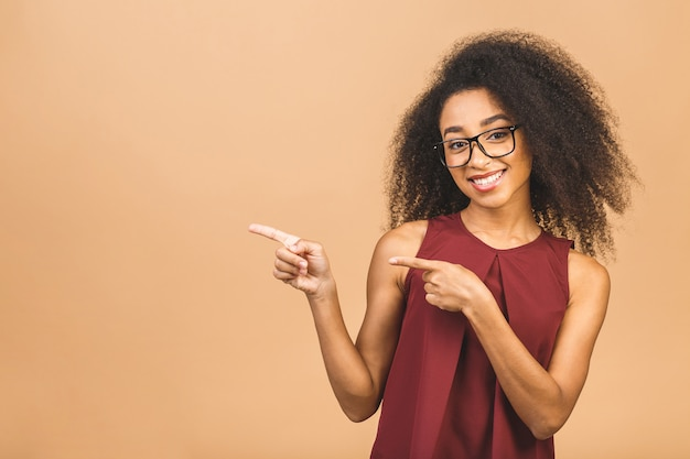 Portrait of a happy young business curly woman pointing fingers away at copy space over beige.