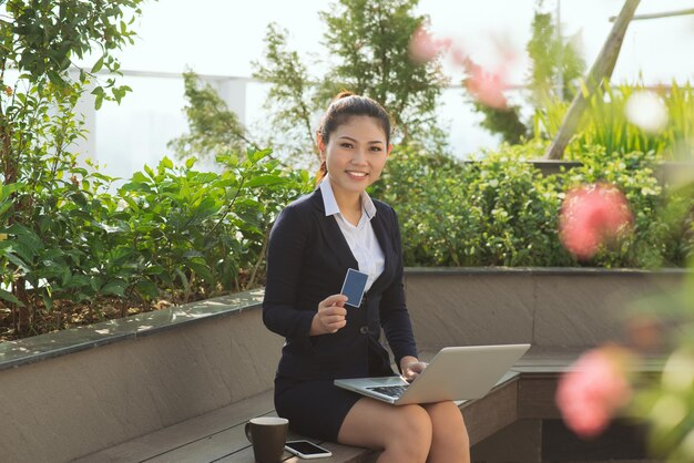 Portrait happy young business woman holding credit card and laptop making online oder, shopping concept isolated outdoors, outside background. positive facial expressions, emotions. smiling customer