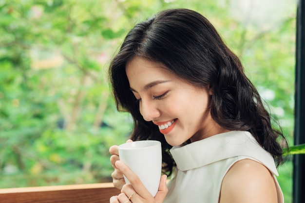 Portrait of happy young business woman with mug in hands drinking coffee and looking on laptop.