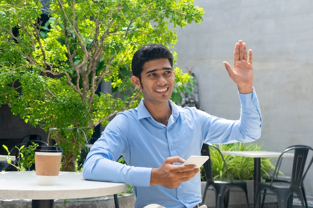 Portrait of happy young businessman greeting colleague outdoors.