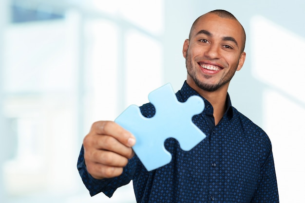 Portrait of a happy young businessman holding jigsaw puzzle