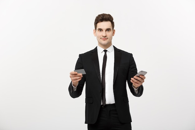 Portrait of happy young businessman in smart black suit standing isolated over white wall background. holding mobile phone and credit card.
