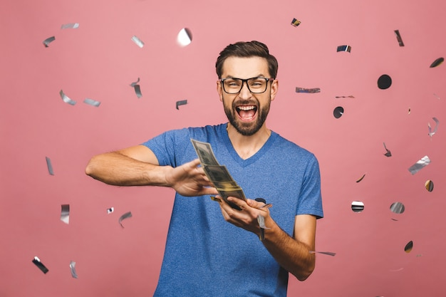 Portrait of a happy young businessman throwing out money banknotes isolated over pink background.