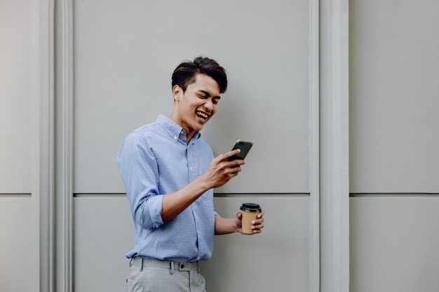 Portrait of a happy young businessman using mobile phone. lifestyle of modern people. standing by the wall with coffee cup