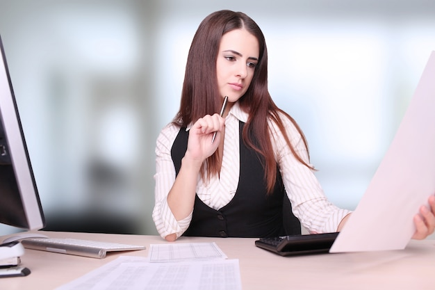 Portrait of happy young businesswoman sitting at desk calculating finance