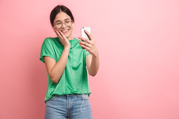 Portrait of a happy young casual girl standing isolated over pink wall, having video call with earphones and mobile phone