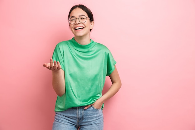 Portrait of a happy young casual girl standing isolated over pink wall, laughing
