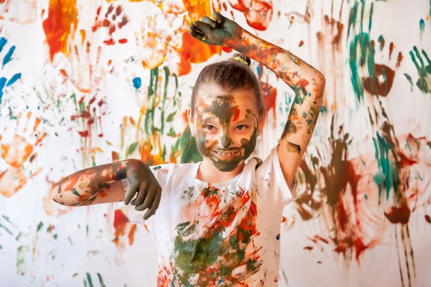 Portrait of happy young child playing with watercolor. child face and clothes randomly painted with paints. concept children fun, art games and hooliganism. color image for holi festival. copy space