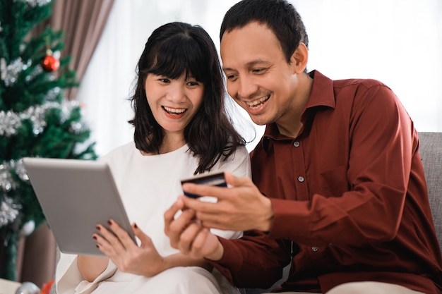 Portrait of happy young couple buying stuff online using credit card in christmas day