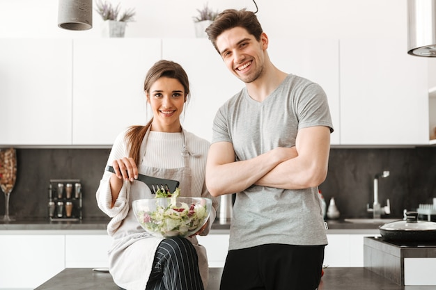 Portrait of a happy young couple cooking salad together