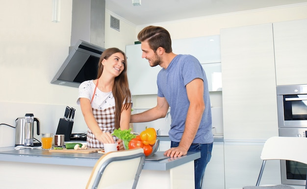 Portrait of happy young couple cooking together in the kitchen at home.