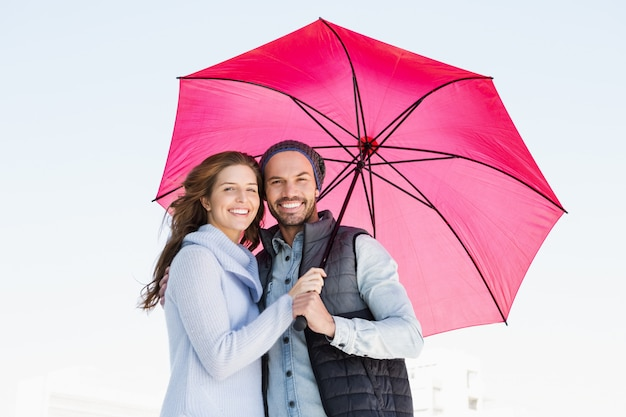 Portrait of happy young couple holding pink umbrella together outdoors