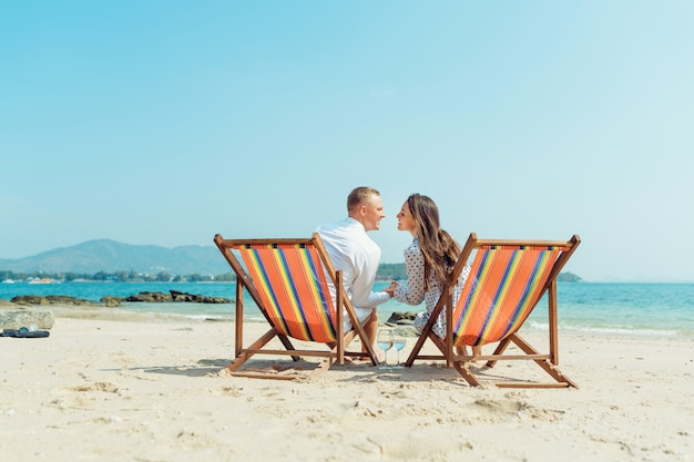Portrait of happy young couple hugging near with deck chairs in luxury beach hotel