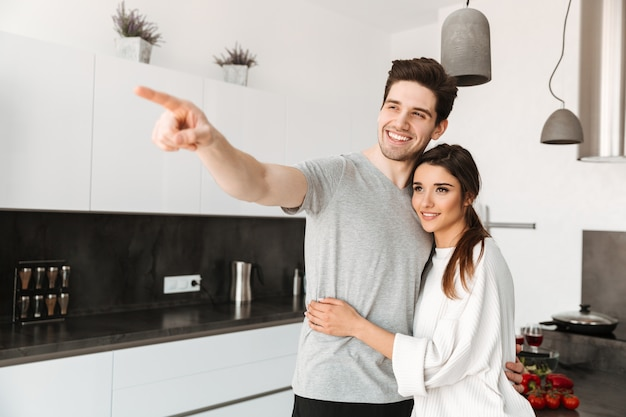 Portrait of a happy young couple hugging and pointing