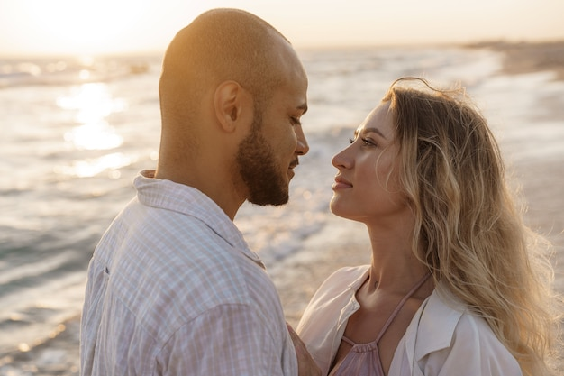 Portrait of happy young couple in love embracing each other on beach Premium Photo