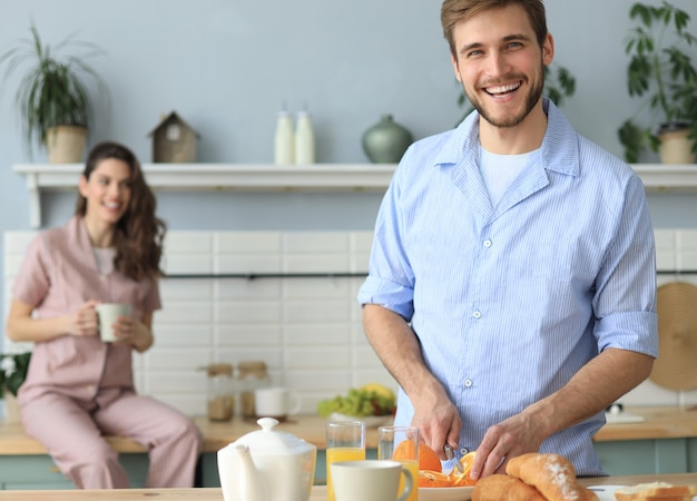 Portrait of happy young couple in pajamas cooking together in the kitchen, drinking orange juice in the morning at home.