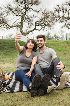 Portrait of happy young couple on picnic taking selfie on cell phone