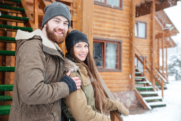 Portrait of happy young couple standing together near wooden cottage in snowy weather