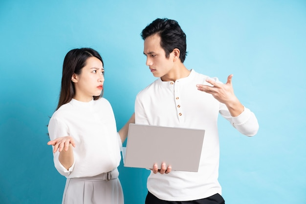 Portrait of happy young couple using laptop on blue wall