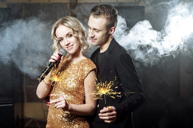 Portrait of happy young couple with sparklers singing with microphone.
