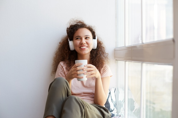 Portrait of happy young curly mulatto lady sitting by the window, drinking tea, listening favorit song at headphones and enjoying the sunny day at home.