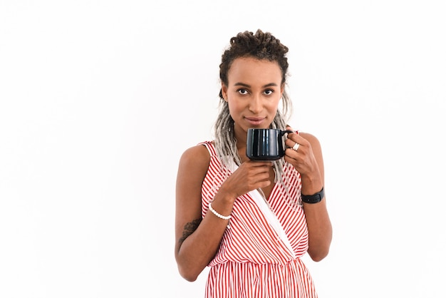Portrait of a happy young cute cheery woman with dreads posing isolated on white drinking coffee or tea.