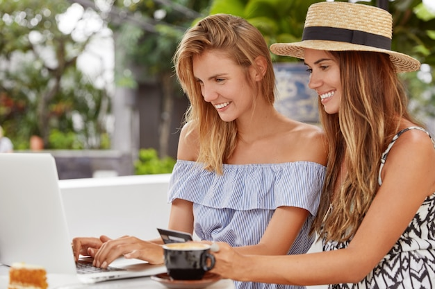 Portrait of happy young european women do shopping online, type number of credit card on laptop computer, pay for purchase online, recreat together in coffee shop, drink hot aromatic beverage