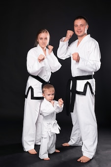 Portrait of happy young family in martial arts uniform standing on black