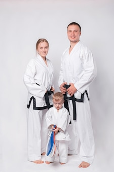 Portrait of happy young family in martial arts uniform standing on white