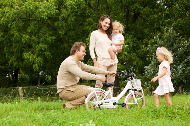 Portrait of happy young family in park with bicycle