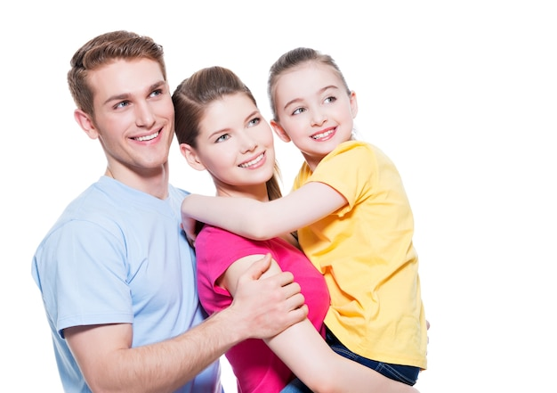 Portrait of the happy young family with child in multicolor shirts - isolated on white wall.