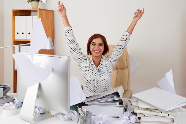 Portrait of happy young female office worker throwing documents celebrating her last day of work