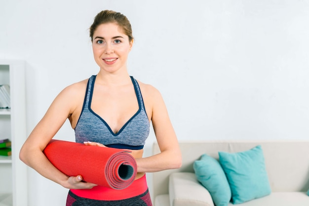 Portrait of a happy young fitness woman holding rolled up exercise mat