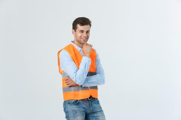 Ritratto di giovane caporeparto felice con la maglia arancio isolata sopra fondo bianco.
