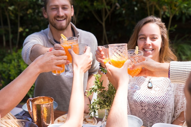 Portrait of happy young friends toasting juice outdoors