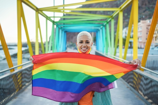 Portrait of happy young gay woman holding lgbt rainbow flag - focus on face