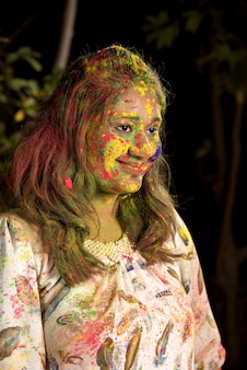 Portrait of a happy young girl on the festival of colors holi. girl posing and celebrating the festival of colors.