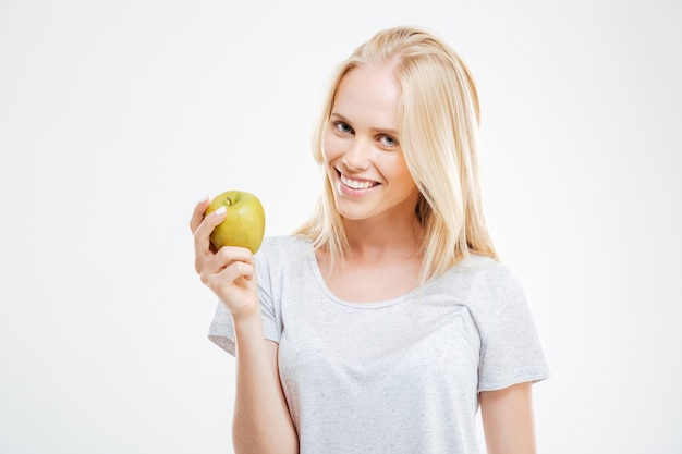 Portrait of a happy young girl holding green apple isolated on a white wall