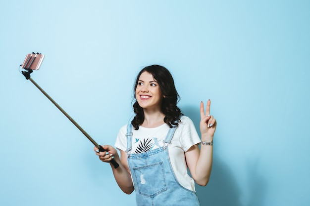 Portrait of a happy young girl making selfie isolated over blue wall