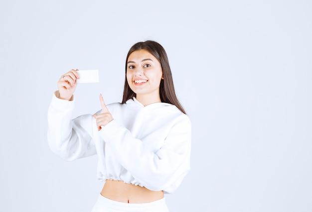 Ritratto di un modello di ragazza felice che punta a una carta.